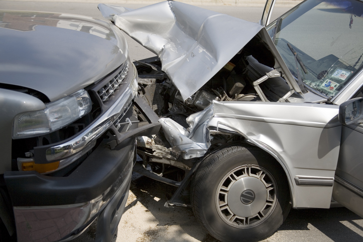 side view of two heavily damaged vehicles involved in a head-on crash