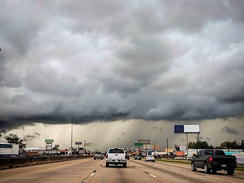 A huge, scary storm sits over Interstate 45 as cars and trucks drive into it.