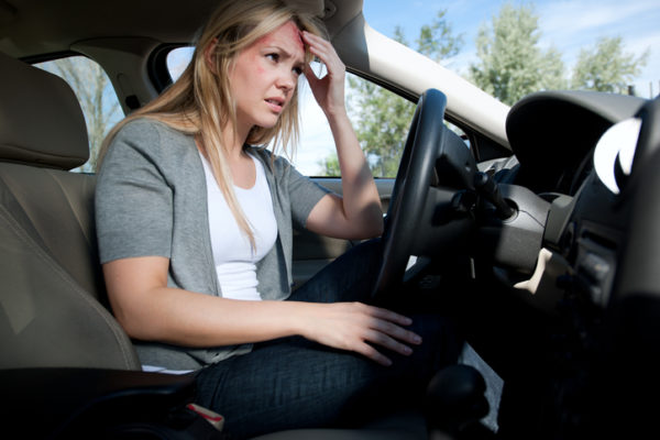 Dazed woman with head wound sitting in car after accident